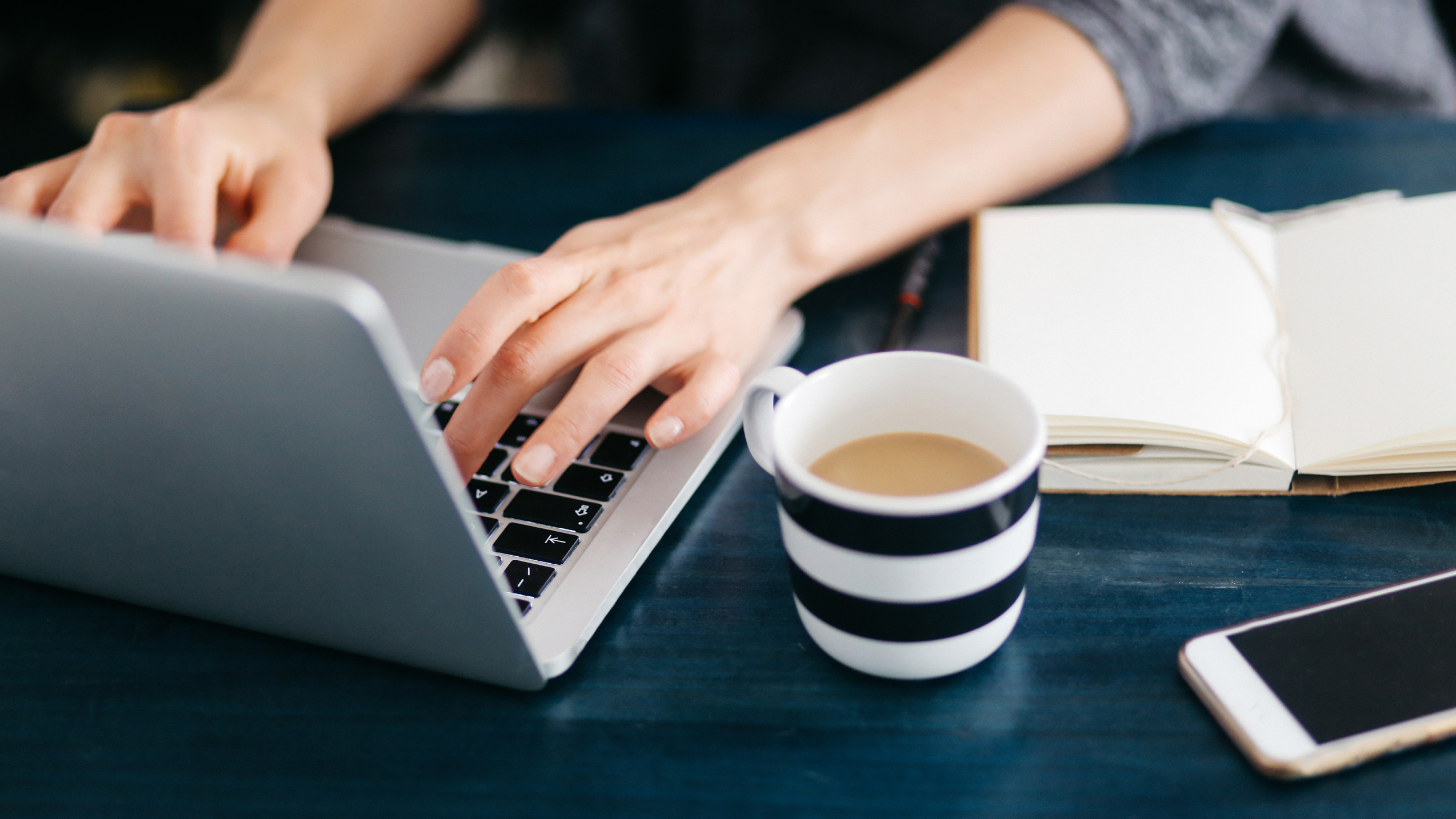 Woman working at a desk with a laptop and a cup of coffee